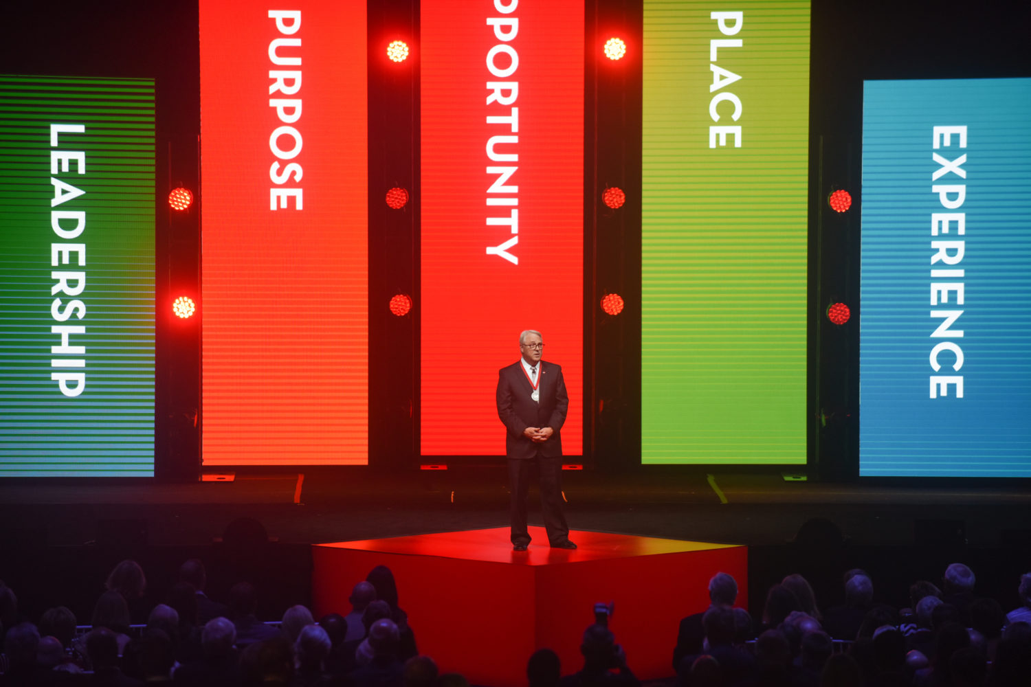 Image of Chancellor Woodson standing in front of the 5 Priorities of the Campaign